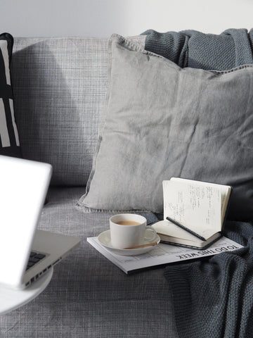 Grey sofa with tea and notebook