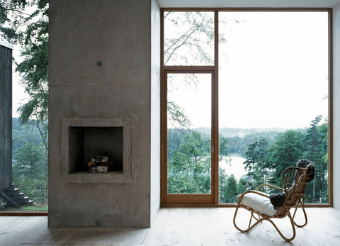 Living room with view over forest. Concrete fireplace and comfy chair