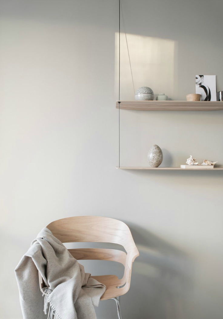 Wooden chair with a blanket and string shelves against a grey wall with patches of sunlight