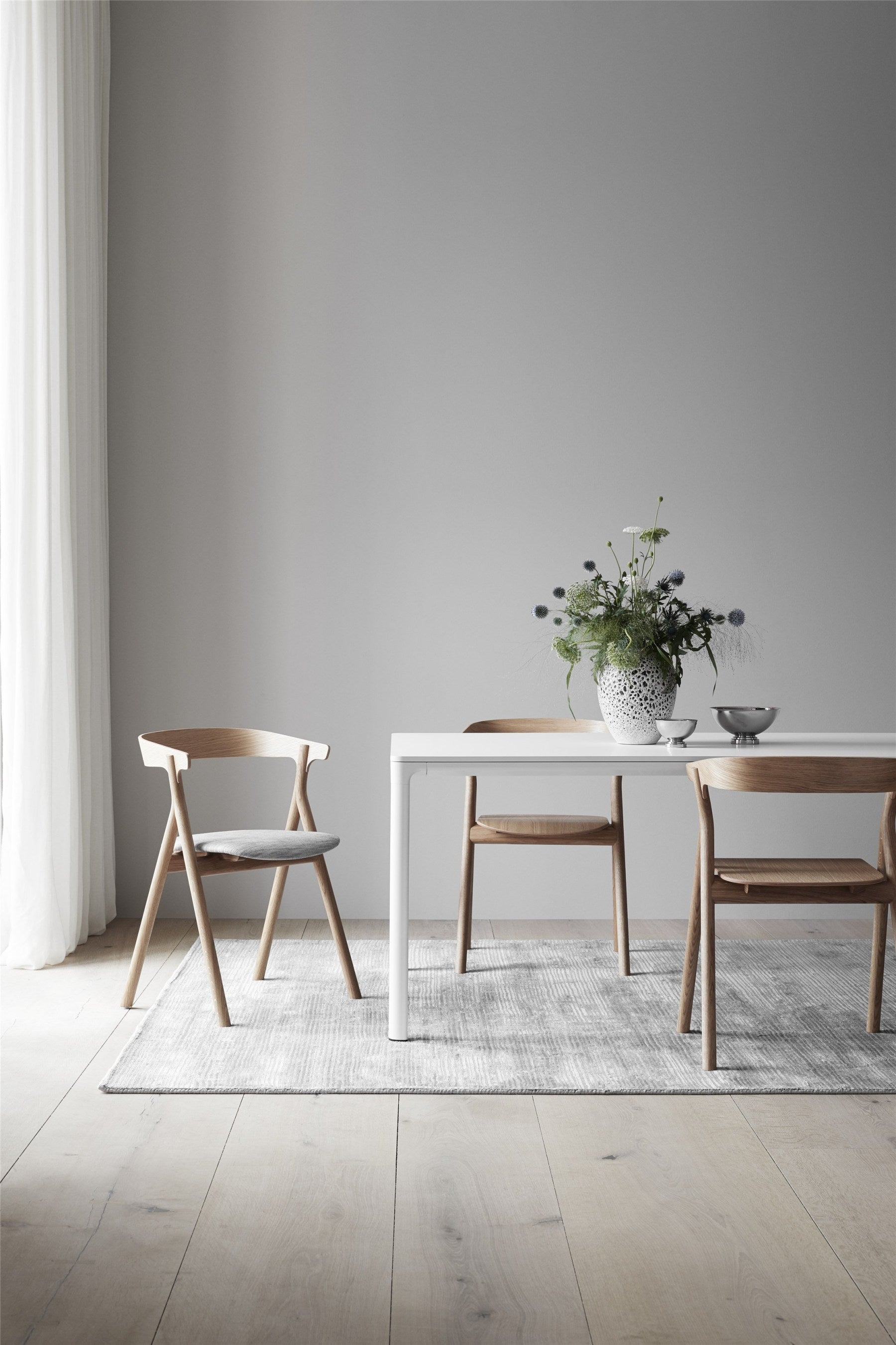 Large dining space lit by very tall window. White table, modern wooden chairs, grey rug, grey walls