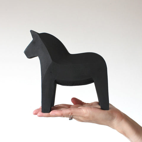 Black Concrete Dala Horse held on a hand