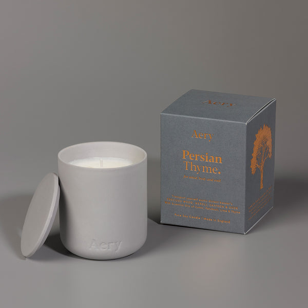 Candle in grey ceramic pot with grey packaging also shown