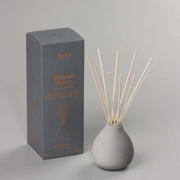 Reed diffuser with pale grey ceramic vase