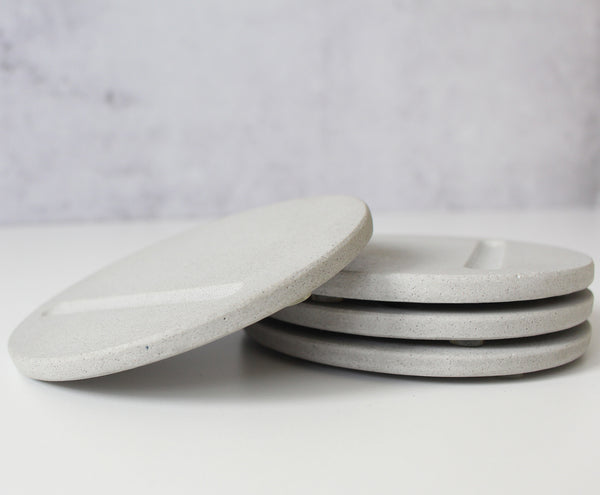 Pile of 4 round pale grey coasters
