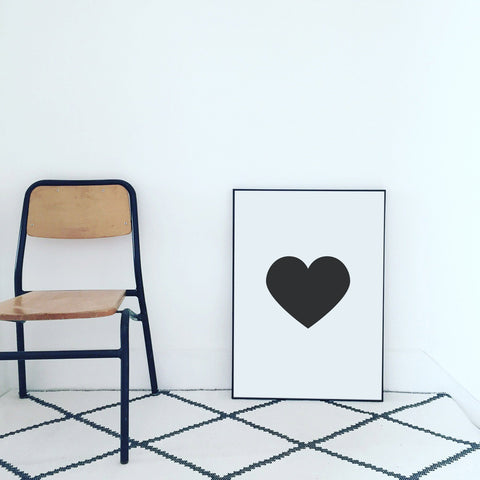 Black heart print next to vintage chair