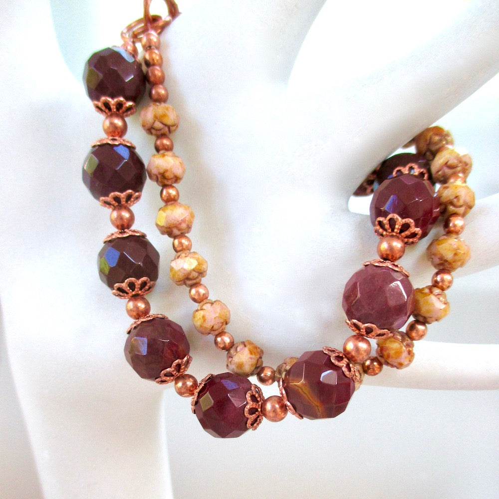 Deep red maroon jasper stones of faceted mookaite, petite beige Czech glass flowers and copper combine to create a casually elegant and sophisticated 2 strand bracelet for modern women with a love of Edwardian and Art Nouveau retro fashion statements. The two strands are securely fastened by our hand forged copper toggle clasp. Unique one of a kind jewelry designed and handmade in Maine, USA, by Rough Magic Creations on Prospero Lane.