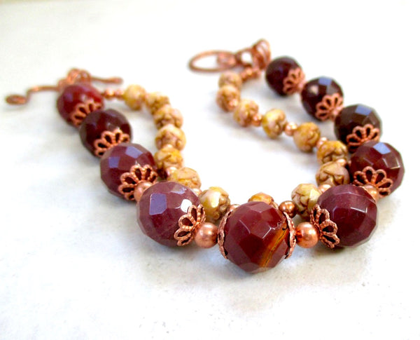 Deep red maroon jasper stones of faceted mookaite, petite beige Czech glass flowers and copper combine to create a casually elegant and sophisticated 2 strand bracelet for modern women with a love of Edwardian and Art Nouveau retro fashion statements. The two strands are securely fastened by our hand forged copper toggle clasp. Unique one of a kind bohoesque jewelry designed and handmade in Maine, USA, by Rough Magic Creations on Prospero Lane.