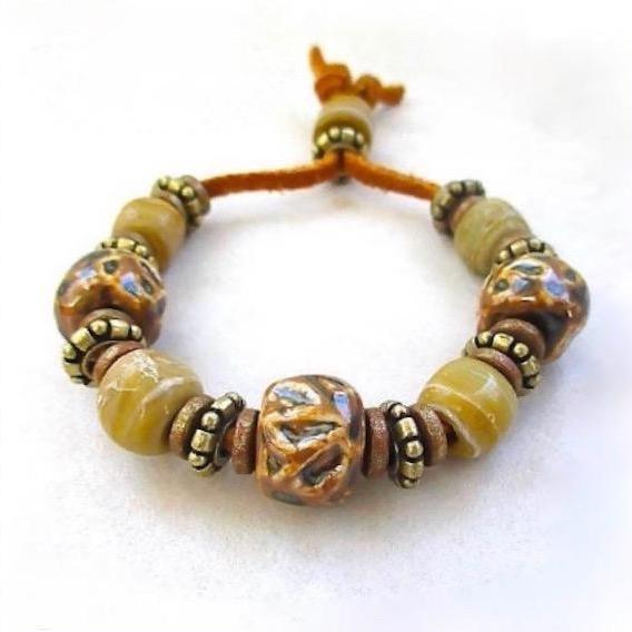chunky bracelet with large beads on a suede cord is sure to please either a man or woman who likes big, bold handmade jewelry in shades of brown, tan and beige.