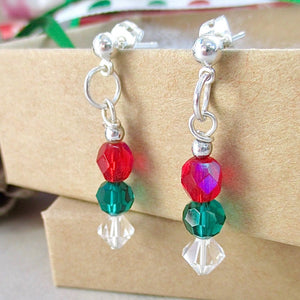 Red green and clear Christmas earrings with stacked dangles and silver components and ball post stud backs, festive holiday jewelry for women designed and handcrafted by Rough Magic Creations for J and M Handmade Jewelry, made in America.