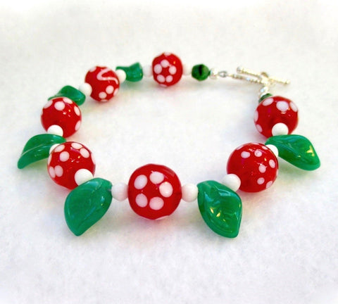 Red Green White Christmas Bracelet, Floral Holiday Jewelry for women, with cherry berry red lampwork with white abstract flower petal dots, bright green Czech glass leaves and dainty snowball beads. Finished with a silver toggle clasp with a romantic heart motif. Designed by Rough Magic Holidays for J and M Handmade Jewelry, made in Maine, USA.