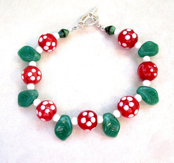 Festive Christmas bracelet red and white lampwork beads, green leaves, seed beads, silver toggle clasp, handmade holiday jewelry.