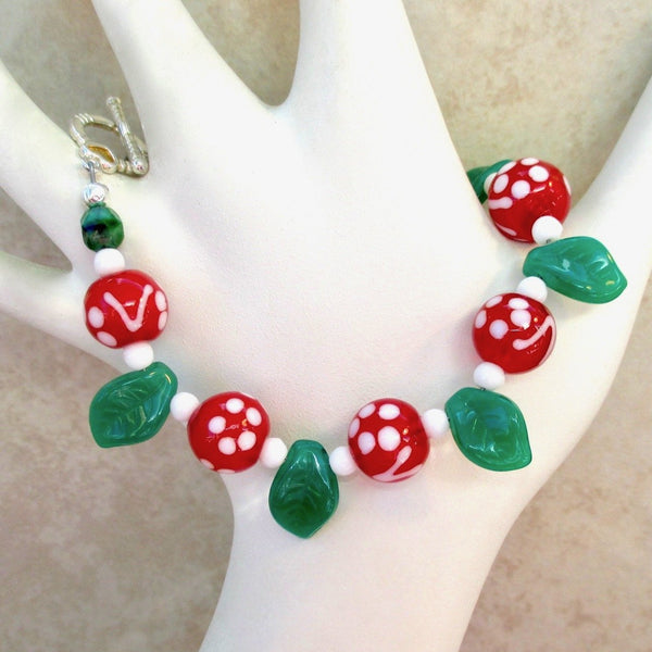 Red Green White Christmas Bracelet handmade holiday jewelry for women with lampwork beads and glass leaves.
