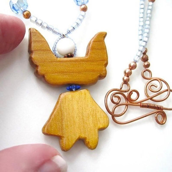 Hand carved natural wood angel pendant, blue beaded necklace, crystals, stars, copper, Christmas jewelry for women. Designed and made in America by Rough Magic Holidays for J and M Handmade Jewelry, handcrafted, made in USA.