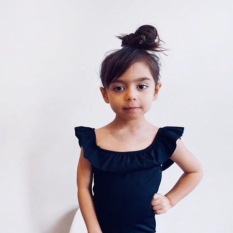 Luna Ruffle Little Girls One Piece in Black by CURRENT. Image via @miss.averyrose