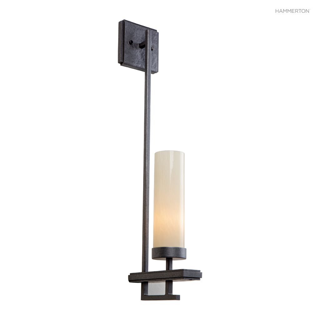 ID2066 Sleek cylinder sconce with design details in hammered and hand-distressed steel. Offered in a choice of acrylic, blown glass or calcite s and 20+ finishes. American handcrafted to order. Can be customized in size, scale or materials.