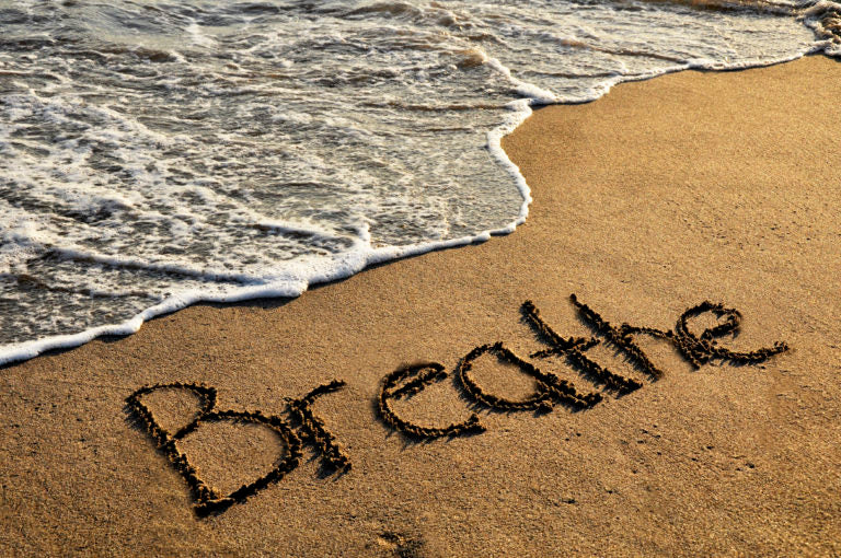 The word breathe written in sand on the beach | HealthMasters