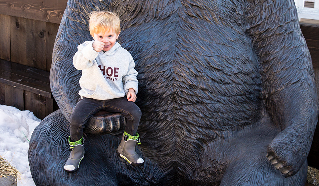 Small boy sits on bear statue