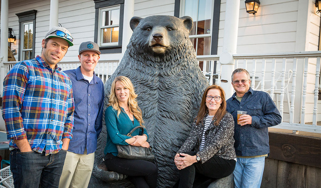 Guests pose with bear statue at Tahoe Quarterly Best of Tahoe release party at Tahoe University in Truckee, CA