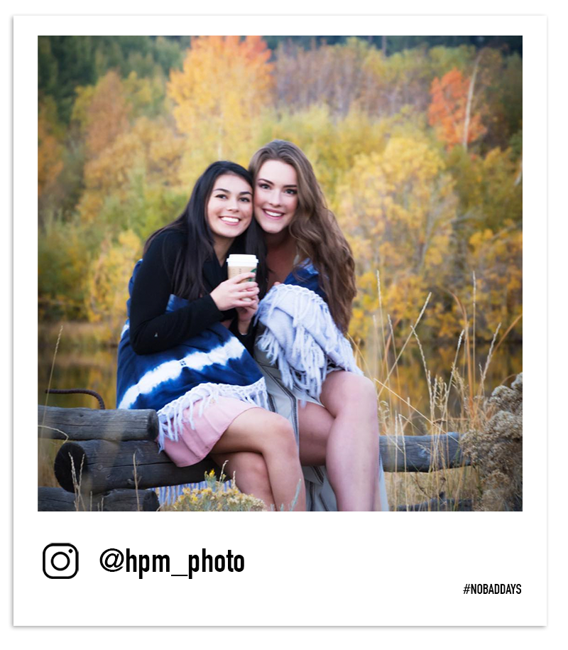 Two girls sip coffee on a fallen tree among fall leaves in Tahoe by @hpm_photos