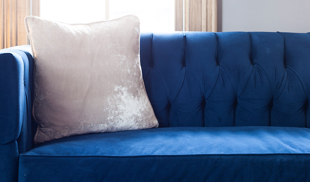 White velvet throw pillow on blue velvet couch at Tahoe University