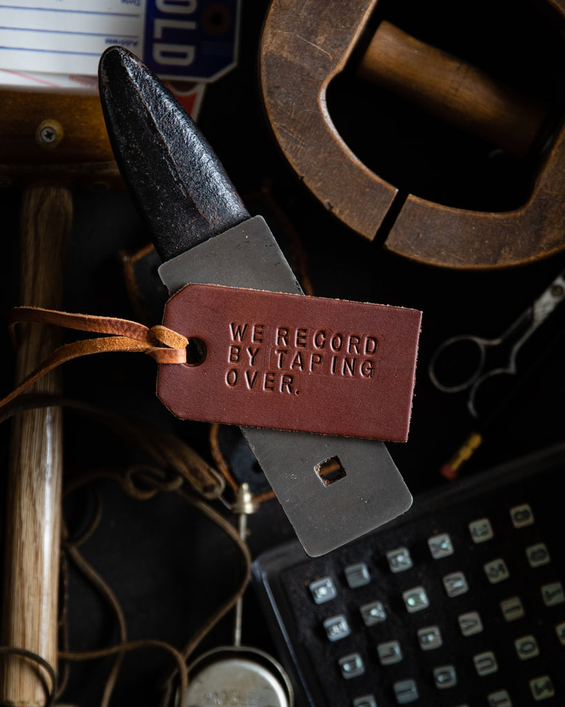 Leather tag with quote by Osita Nwanevu