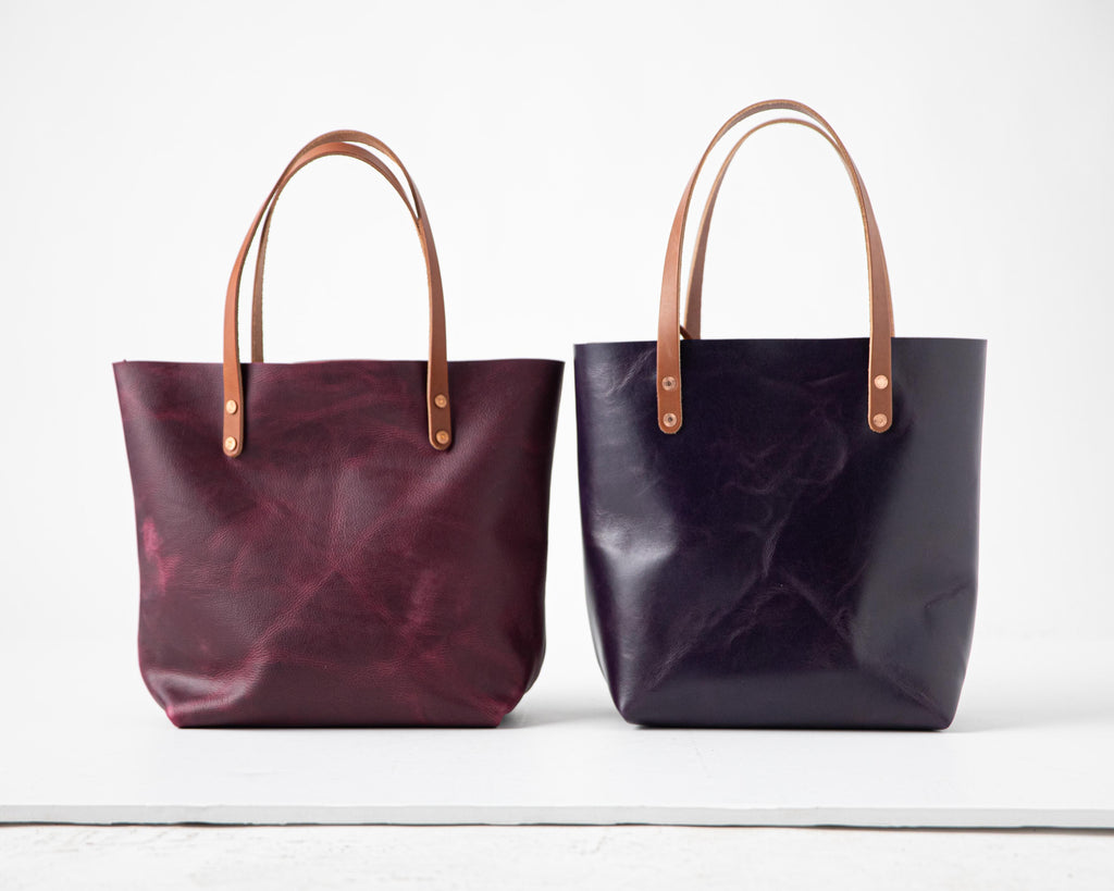 Purple Kodiak leather tote bag on left, Orchid leather tote bag on right