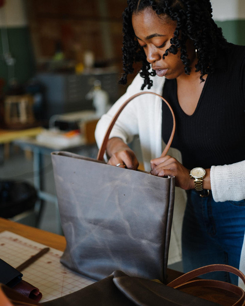 Alexis putting handles on a leather tote bag
