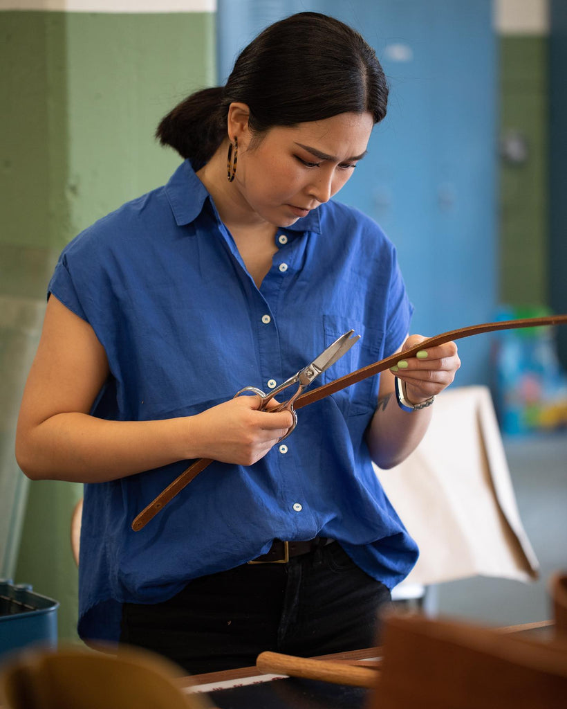 Juhyun trimming the handle of a leather tote bag