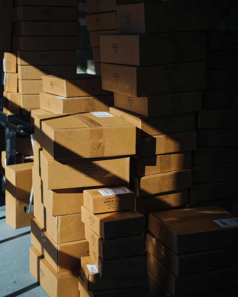 Cardboard boxes containing leather tote bags from KMM & Co.