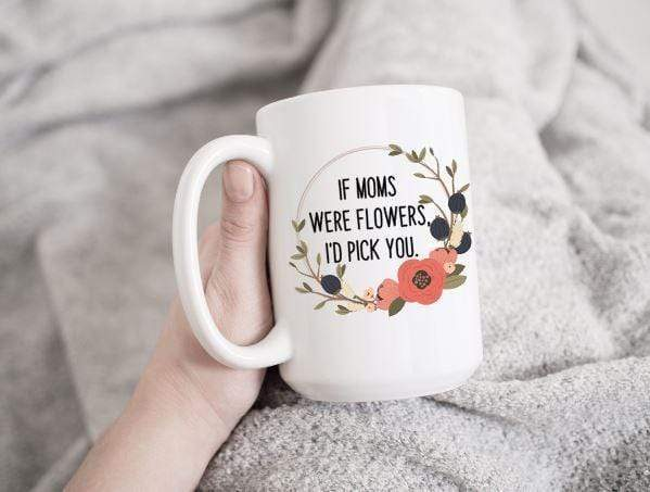 15 oz white ceramic coffee mug slanted back being held by a hand with a grey blanket in the background