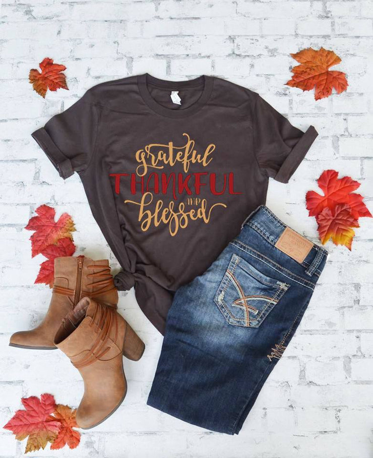 brown short sleeve Grateful Thankful Blessed T-Shirt tied on the side in a knot laid flat with folded jeans to right and brown boots to lower left fall leaves scattered and white and grey brick background