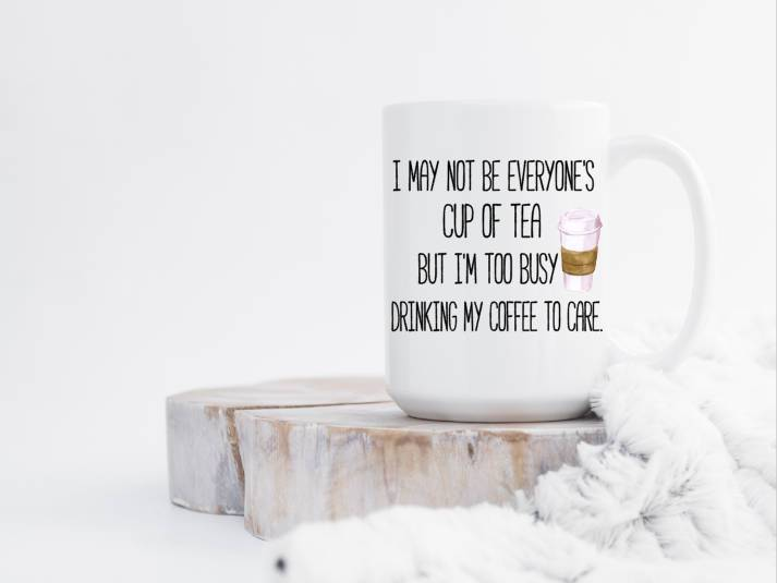 white ceramic coffee mug with handle to the right i may not be everyone's cup of tea but i'm too busy to care printed on front mug sitting on white wash slab of wood with a blanket cuddled up to it
