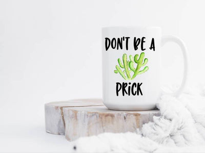 15 oz white ceramic coffee mug handle to the right Dont be a Prick in black with a green cactus in center mug is sitting on a white wash wood slab with a white blanket snuggled up to the wood and mug