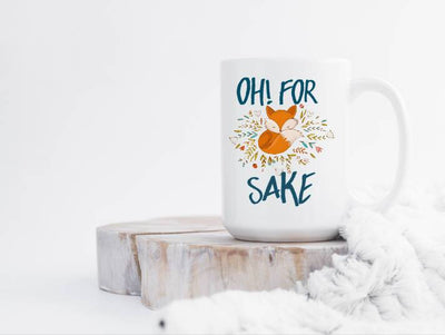 Oh for fox sake coffee mug featuring an orange fox with colorful small leaves around the fox
