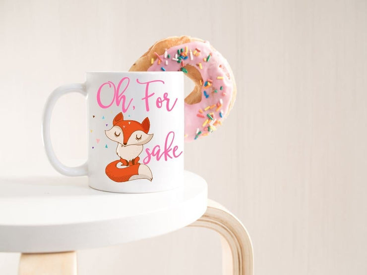 Oh, for fox sake in pink text featuring a orange and tan fox with sassy folded arms and eyes closed on a white ceramic coffee mug on table