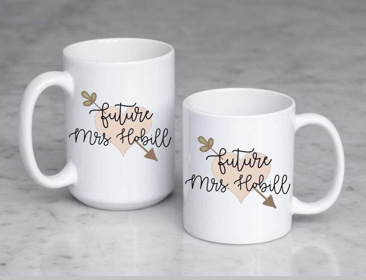 Future Mrs. with last name in black text on top of peach heart with leafy arrow poking through in olive green displays both size mugs