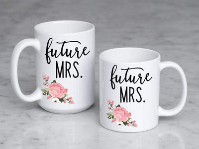 future mrs. in black text with pink and green floral bottom left printed on 11 oz and 15 oz ceramic mugs side by side