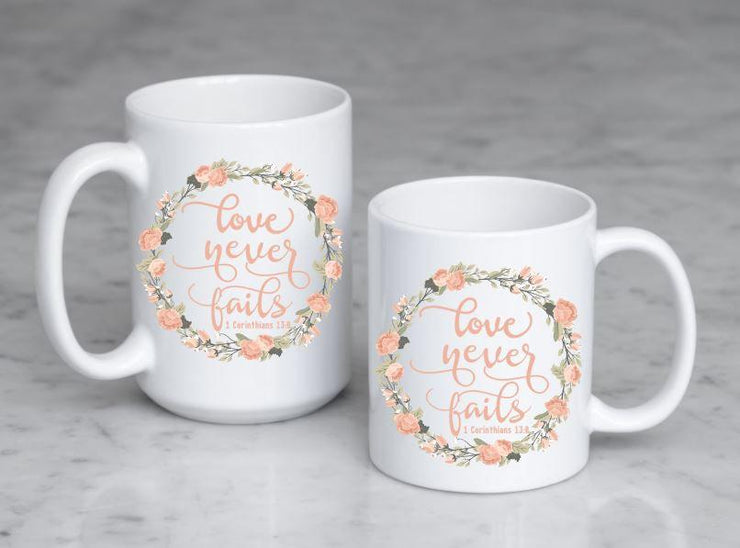 love never fails corinthians 13:8 quote in peach or olive with peach and olive floral wreath on ceramic mug on 2 mug sizes