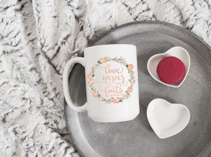 love never fails corinthians 13:8 quote in peach text with peach and olive floral wreath on ceramic mug