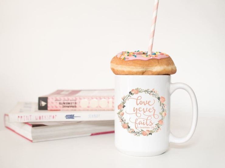 love never fails corinthians 13:8 quote in peach or olive with peach and olive floral wreath on ceramic mug straight on pic with donut and books