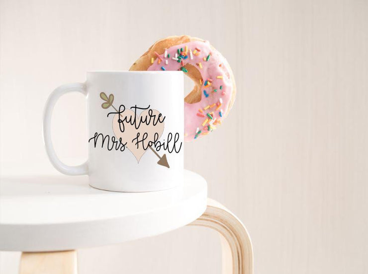 Future Mrs. with last name in black text on top of peach heart with leafy arrow poking through in olive green on edge of white table with donut hanging on side of mug with pink frosting and sprinkles
