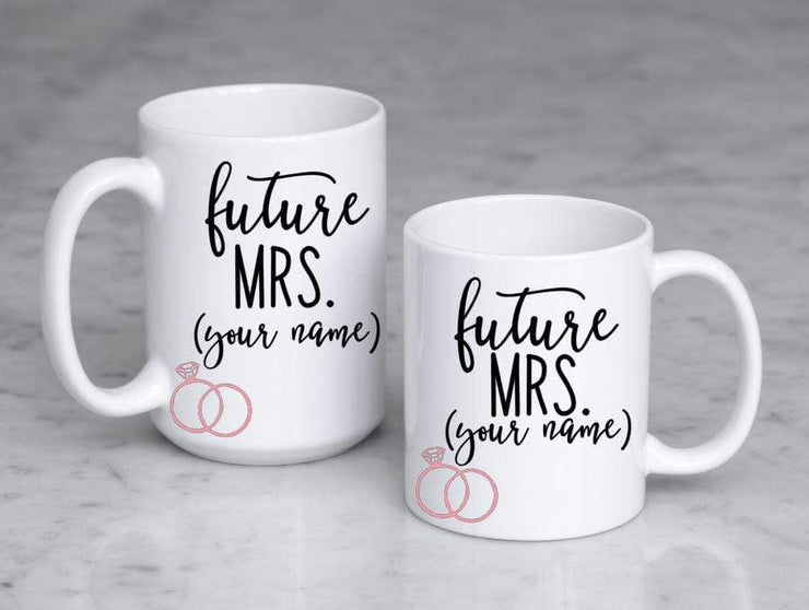 future mrs. with spot for personalizing in black text featuring 2 pink rings on white ceramic coffee mugs sized 11 oz and 15 oz