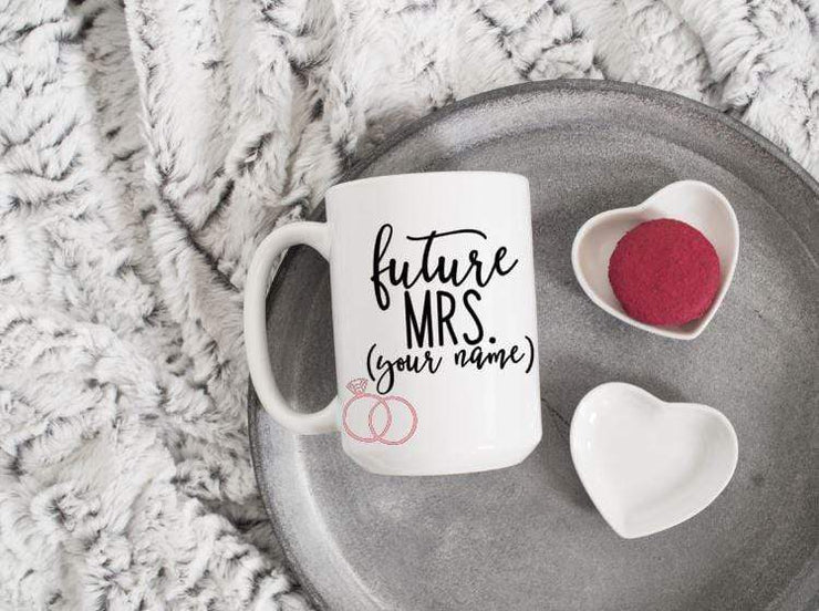 future mrs. with spot for personalizing in black text featuring 2 pink rings on white ceramic coffee mug