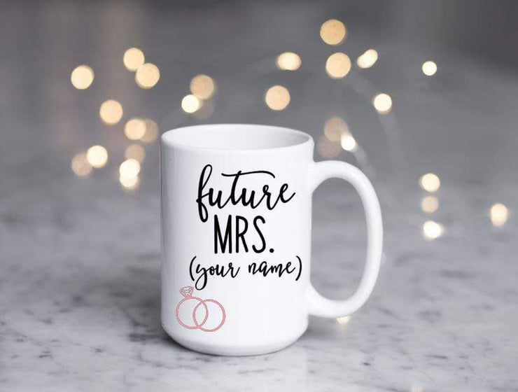 future mrs. with spot for personalizing in black text featuring 2 pink rings on white ceramic coffee mug with fake glitter popping out the top