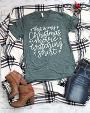 this is my christmas movie watching tee in white lettering on a green marble vneck t-shirt with jeans and boots on side of shirt