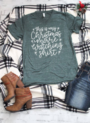this is my christmas movie watching tee in white lettering on a green marble vneck t-shirt with jeans and boots to the side of shirt