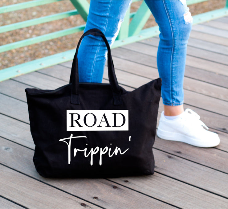 Road trippin' white words on large black tote bag next to womans leg