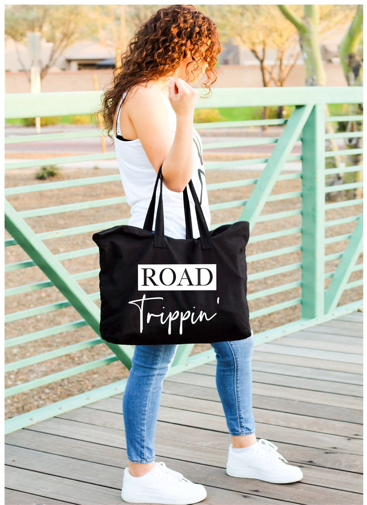 Road trippin' white words on large black tote bag hanging on womans arm