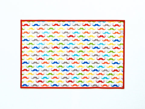 Little Dragon by Lauren Unlimited red, aqua, blue, green, yellow and orange moustache laminated cotton placemat