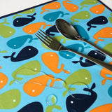 Little Dragon by Lauren Unlimited aqua blue, navy, green and orange whale laminated cotton placemat close up image with water droplets and children's cutlery